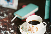 A teacup and saucer beside small colorful notebooks