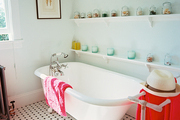 A claw-foot tub soaks up the sun next to jars of seashells and a patterned tile floor.