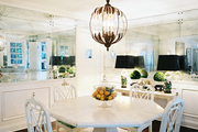 Mirrored walls and a white table and chairs in a dining space