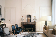 A zebra hide and antique chairs in a formal living space