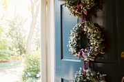 A black front door decorated with a trio of wreaths