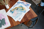 An overhead of abstract paintings on a table.