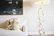 A floor lamp made of antlers beside a white couch