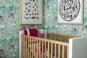 Bright wallpaper and framed art above wood crib.