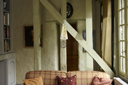Painted wood beams above plaid couch.