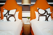 A pair of twin beds with orange headboards in front of a striped wall