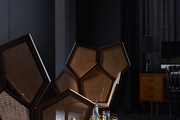 A pair of caned honeycomb chairs in a moody bedroom