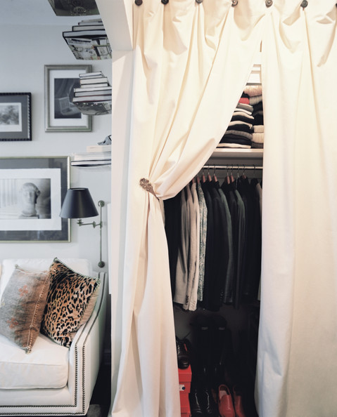 Organization - Flowing white curtains in front of an organized closet
