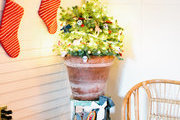 A rattan seatee in a small space with holiday items around it.