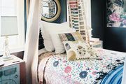 A brass canopy bed dressed with floral linens