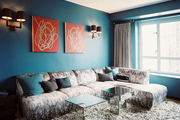Blue walls and a gray sectional with a pair of mirrored tables in a den