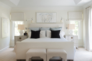 Tonal bedroom with white bedding and a lofted ceiling.