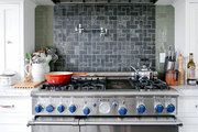 a tile backsplash above a stainless steal oven