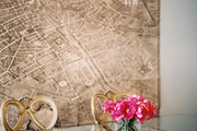 A vintage map of Paris in a dining space filled with a crystal chandelier and a glass table