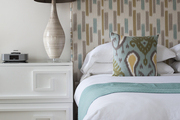 A mixture of patterns in shades of blue, gray, and gold in a guest room