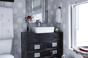 Geometric-patterned wallpaper in a bathroom.