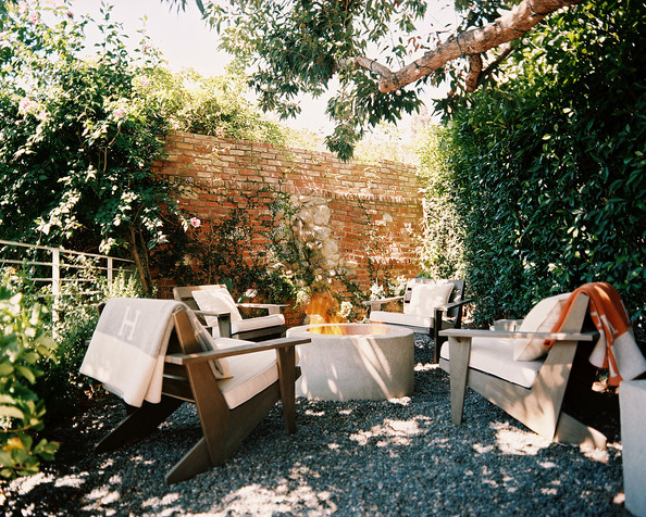 Patio - Four outdoor chairs gathered around a fire pit beside a brick wall