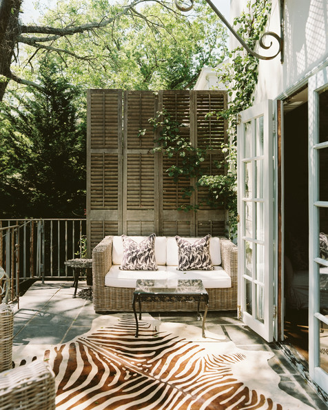Patio - French doors leading to a patio with a wicker couch and a zebra hide