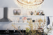 A chandelier shaped like a ship in a kitchen with open shelving and black countertops