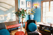 Blue walls contrasted by a pair of red chairs and a red pouf