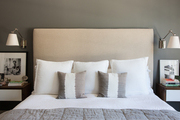 Beige headboard on above white and grey bedding.