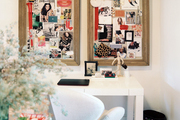 A pair of inspiration boards above a white Parsons desk and an upholstered desk chair
