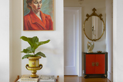 A decorative hallway with wall art and a plant to compliment the space.