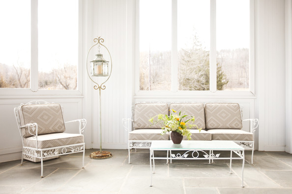 Porch - A vase of flowers and white patio furniture in a screened-in porch