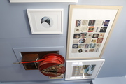 Framed art and a vintage fire hose hang on a blue wall.