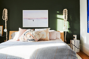 A contemporary bedroom with a dark green wall.