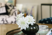 A little vase with flowers on a coffee table.
