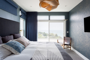 A contemporary bedroom with blue walls.