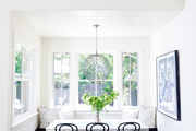 A modern farmhouse style dining space with black bistro chairs.