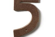 An Arts & Crafts-style address number in bronzed metal