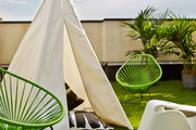 A tepee with outdoor pillows, two Baby Acapulco Chairs in Cactus, and an Eames elephant on Irene Edwards's rooftop patio