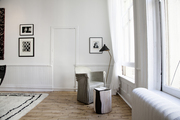 A quiet corner of a white-painted, sparely furnished living room