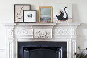 A fireplace mantel topped with artwork