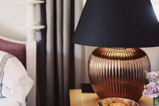 A bedside table topped with a gold lamp with a black shade