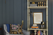 A houndstooth armchair next to a bamboo-style set of shelves against a wall painted in dark paint