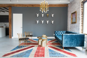 Eclectic living area with vintage furniture and gold chandelier.
