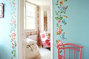 A pink chair beside blue walls decorated with flowers