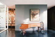 A grand piano and a bookcase with a ladder in a living space