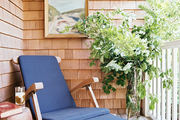 A wooden chair on the balcony of a home with shingle siding