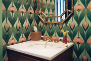 Floral wallpaper and a gold faux-bamboo mirror in a powder room