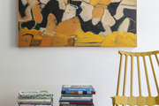 A bench topped with stacks of books beside a yellow chair