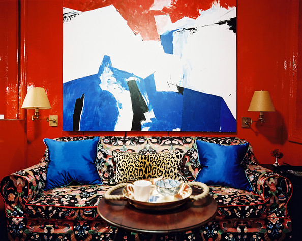 Red Living Room - A floral couch with a leopard-print pillow against red lacquered walls