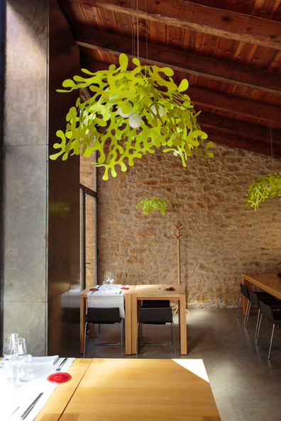 Restaurants - A futuristic chandelier hanging above a pair of Parsons tables