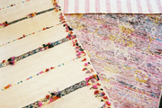 Layered rugs in shades of pink, white, and black