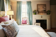 Blue curtains and a white cane-back chair in a bedroom