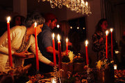 Tall taper candles and a crystal light fixture illuminate a long table of hors d'oeuvres